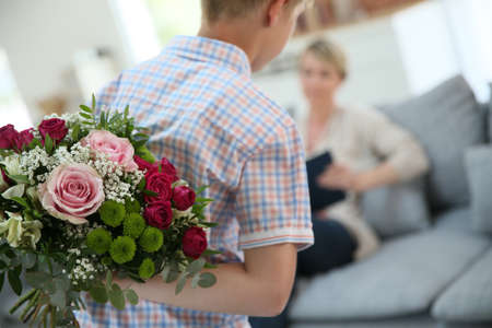 mother child: Son hiding bouquet to surprise mommy on mothers day
