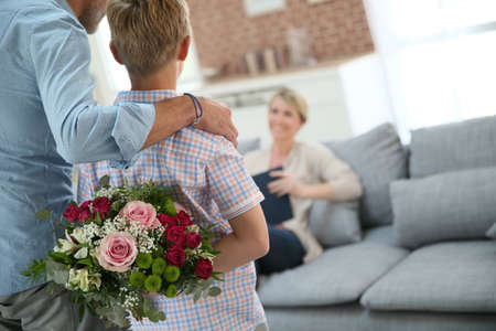 gift behind back: Son hiding bouquet to surprise mommy on mothers day