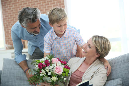 ladies day: Young boy giving flowers to mommy for mothers day