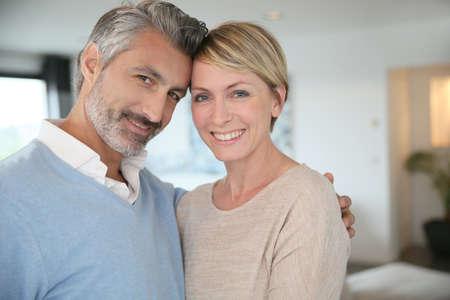 pareja abrazada: Sonriente pareja de mediana edad de pie en casa nueva