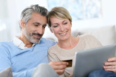 epayment: Cheerful mature couple e-shopping on internet