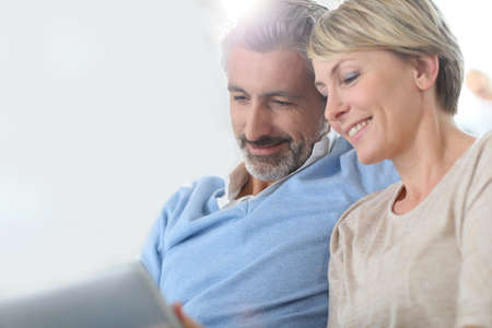beard woman: Middle-aged couple websurfing on internet with touchpad