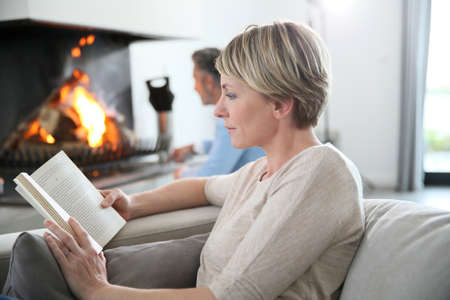 cold woman: Middle-aged woman reading book by fireplace Stock Photo