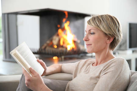 couches: Middle-aged woman reading book by fireplace Stock Photo