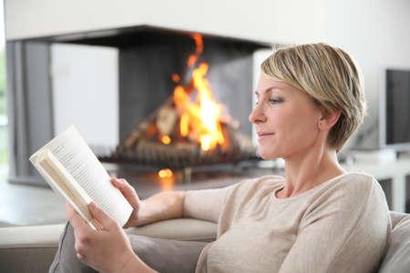 relaxando: Mulher de meia-idade que lê o livro pela chaminé