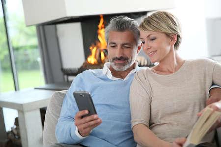 mujer alegre: Pareja de edad media que usa smartphone en casa por la chimenea