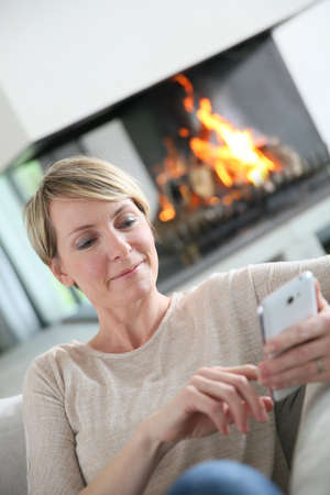 message sending: Middle-aged woman sending message with smartphone
