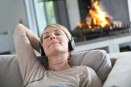 earphone: Woman listening to music by fireplace