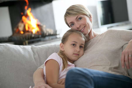 fireplace: Mother and daughter relaxing by fireplace, laying in couch Stock Photo