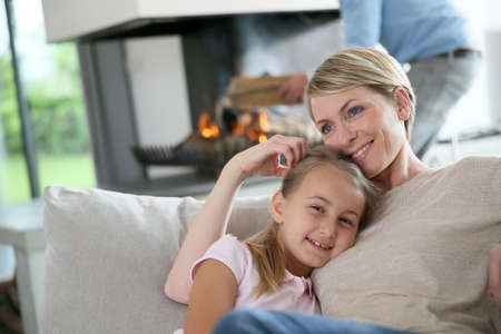 fireplace home: Mother and daughter relaxing by fireplace, laying in couch Stock Photo