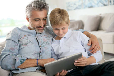 2 years old: Father and son using digital tablet at home