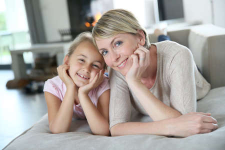 Portrait of mother and daughter laying in couch at home photo