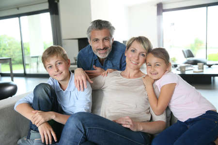 family sofa: Happy family in contemporary house