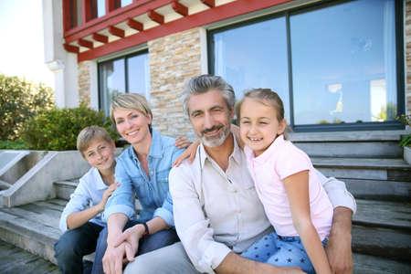 Happy famille de quatre assis en face de la maison contemporaine Banque d'images