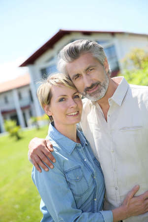 owned: Couple standing in front of newly owned house Stock Photo