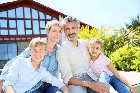 Happy famille de quatre assis en face de la maison contemporaine