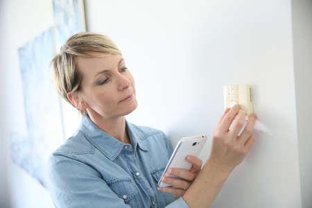 여자 스마트 폰 응용 프로그램과 실내 온도를 porgramming