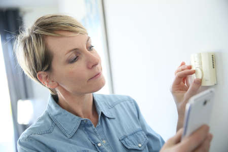 Kobieta porgramming temperaturę w pomieszczeniu z smartphone aplikacji