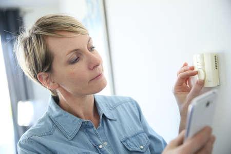 Mujer porgramming temperatura interior con la aplicación de teléfono inteligente