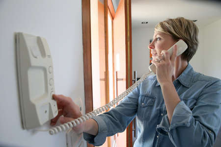 answering: Woman inside home answering intercom