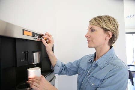 expresso: Middle-aged woman using expresso coffee machine