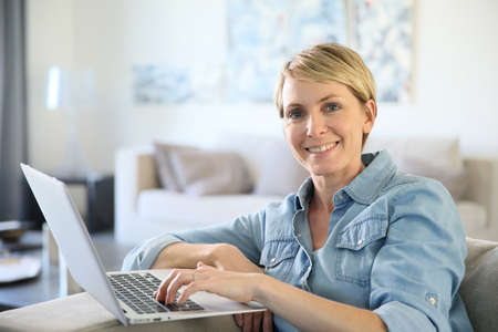 blond woman: Middle-aged woman sitting in sofa and using laptop Stock Photo