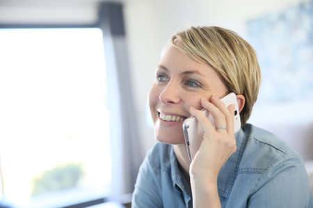 fourties: Middle-aged blond woman talking on phone at home