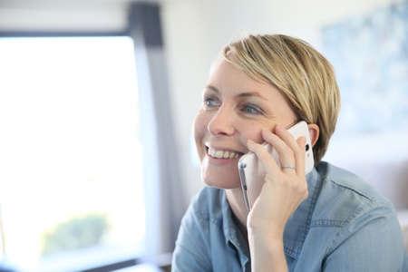 llamando: Mujer rubia de mediana edad hablando por teléfono en casa Foto de archivo