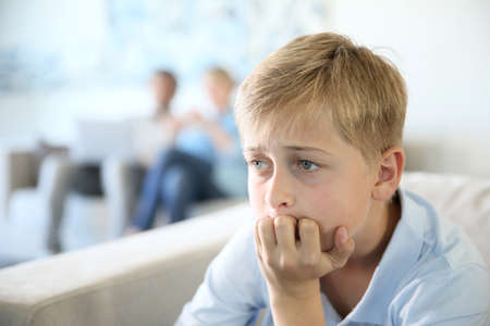 12-year-old boy sitting in couch at home, parents in background