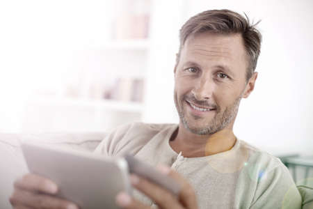 home buying: Handsome smiling man at home buying on internet