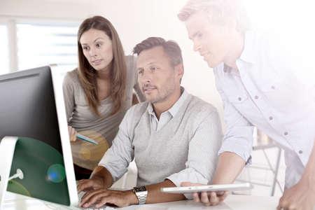 Business people in office working on desktop photo
