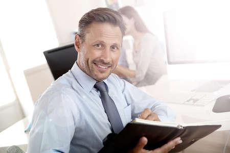 Portrait of handsome businessman holding agenda photo