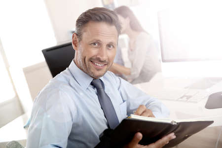 meeting agenda: Portrait of handsome businessman holding agenda Stock Photo