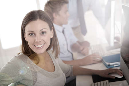 workmates: Woman in business training sitting in front of desktop