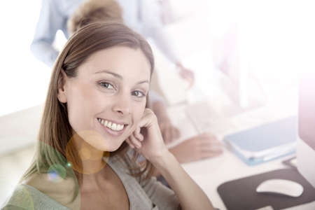 Woman in business training sitting in front of desktop photo