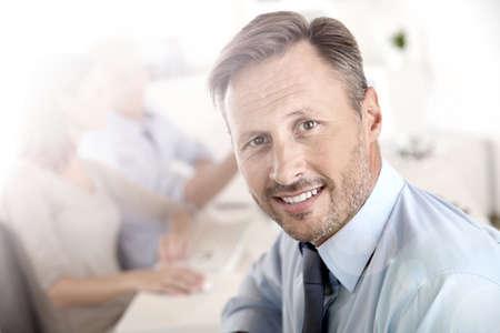 manager: Business Manager mit Mitarbeitern im Hintergrund