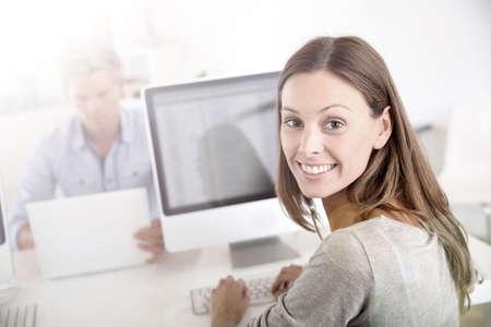 Portrait of smiling office worker in front of desktop photo
