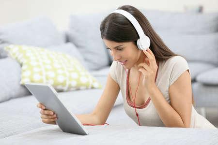 audifonos: Mujer joven con la tableta y los auriculares sentado en el piso Foto de archivo