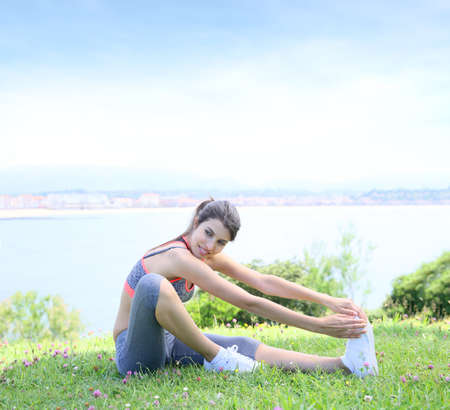 woman stretching: Young fitness woman doing stretching exercises outside