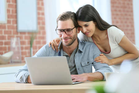 guy with laptop: Couple at home websurfing on laptop computer Stock Photo