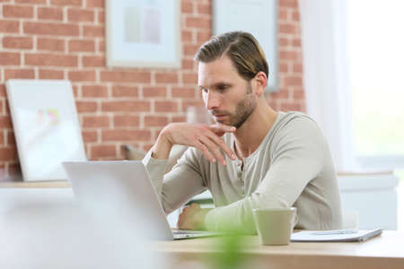 websurfing: Blond guy sitting in front of laptop computer at home