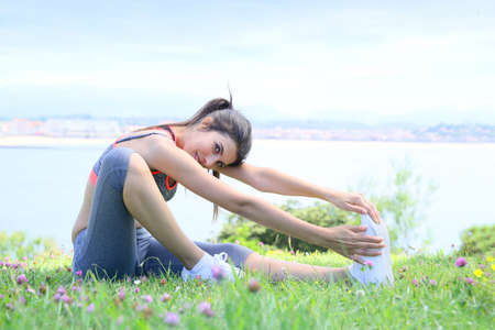 WOMAN FITNESS: Young fitness woman doing stretching exercises outside