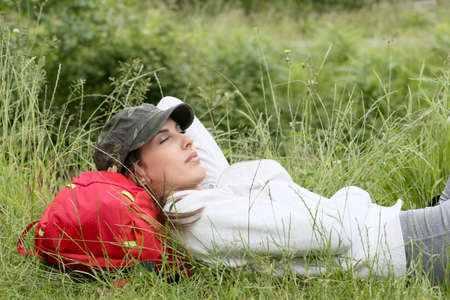 shut down: Young woman relaxing in grass on hiking day Stock Photo