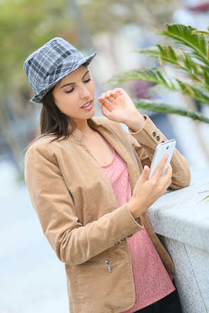 message sending: Beautiful trendy girl sending message with smartphone