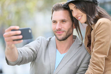 Cheerful young couple taking selfie picture with smartphone photo