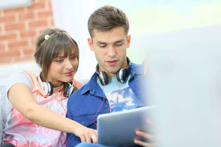 websurfing: Young couple in sofa websurfing with tablet Stock Photo