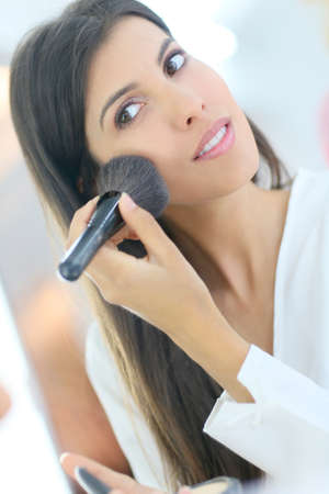Brunette woman using powder brush in front of mirror photo