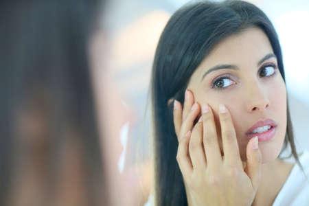 espejo: Hermosa chica morena mirando a la piel en el espejo
