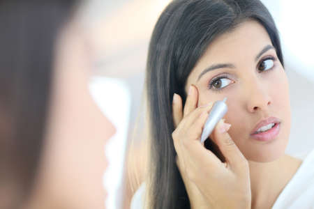 beautycare: Portrait of beautiful woman using cosmetics