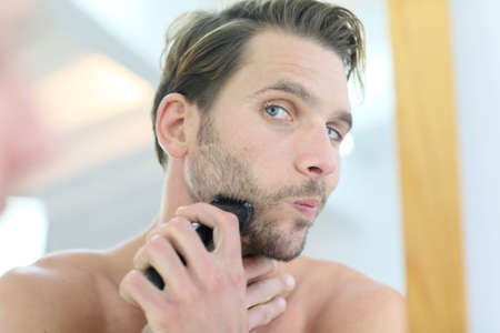 electric razor: Man in front of mirror using electronic shaver